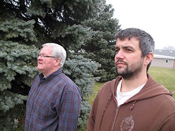 Jeff Browning (left) and Jon Pittman gaze at tornado damage that occurred near the church they serve in Washington, Illinois.